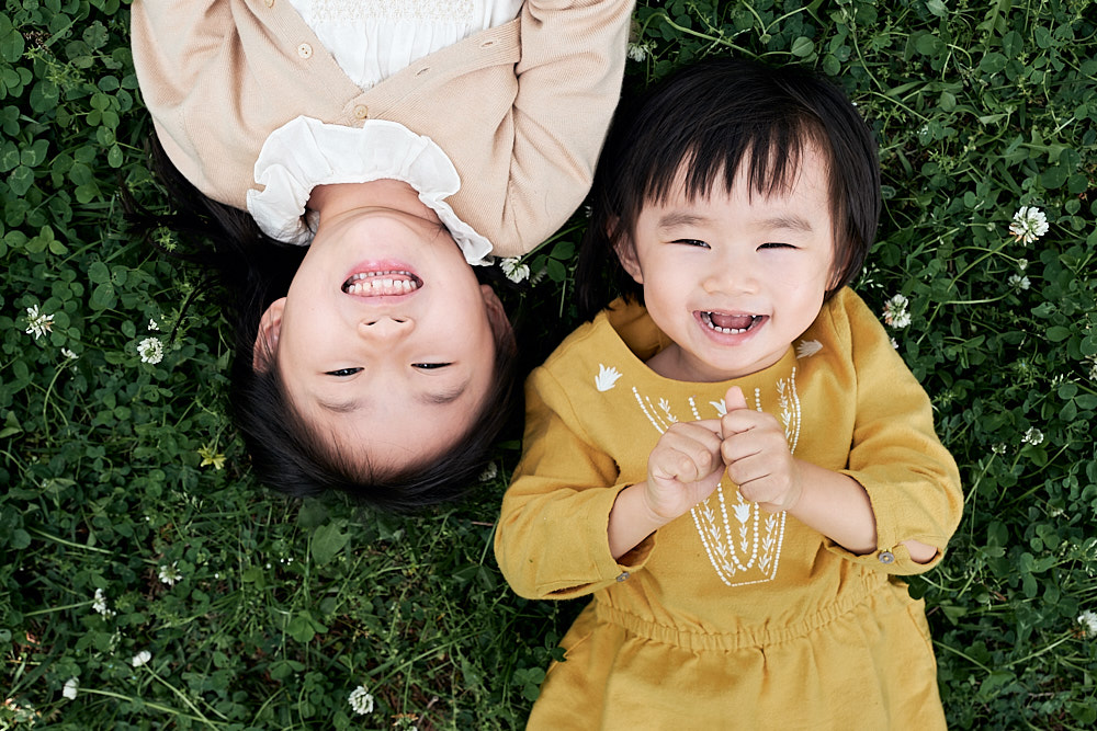 Sisters lying in grass together - Seoul Family Photographer